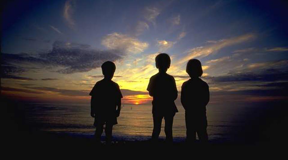 Silhuetter av barn vid vatten i solnedgång
