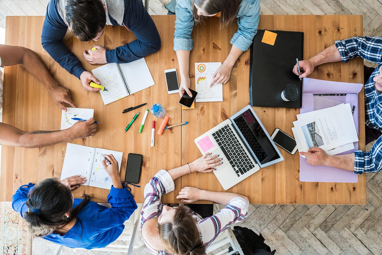 Personer som arbetar tillsammans med datorer och kontorsmaterial