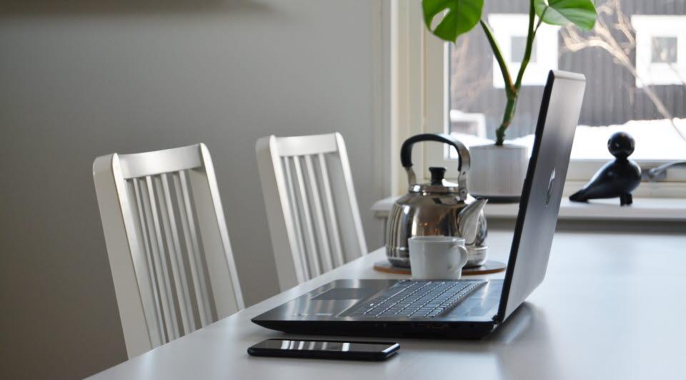 En dator på ett köksbord. Intill ligger en mobiltelefon. En kopp kaffe och en kaffepanna står framme.